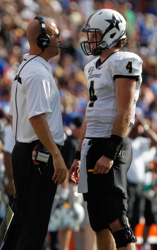 Nov 9, 2013; Gainesville, FL, USA; Vanderbilt Commodores head coach James Franklin talks with quarterback Patton Robinette (4) against the Florida Gators during the second quarter at Ben Hill Griffin Stadium. Mandatory Credit: Kim Klement-USA TODAY Sports