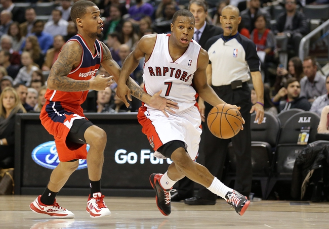 Nov 22, 2013; Toronto, Ontario, CAN; Toronto Raptors point guard Kyle Lowry (7) drives past Washington Wizards guard Eric Maynor (6) at Air Canada Centre. The Raptors beat the Wizards 96-88. Mandatory Credit: Tom Szczerbowski-USA TODAY Sports