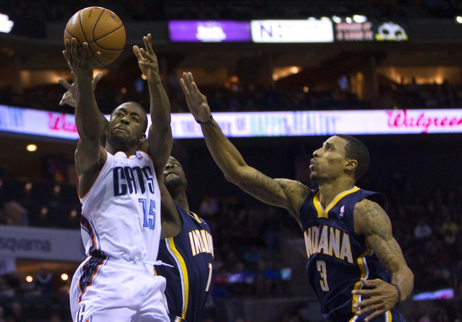 Nov 27, 2013; Charlotte, NC, USA; Charlotte Bobcats point guard Kemba Walker (15) goes in for the basket while being defended by Indiana Pacers point guard George Hill (right) during the second quarter at Time Warner Cable Arena. Mandatory Credit: Joshua S. Kelly-USA TODAY Sports
