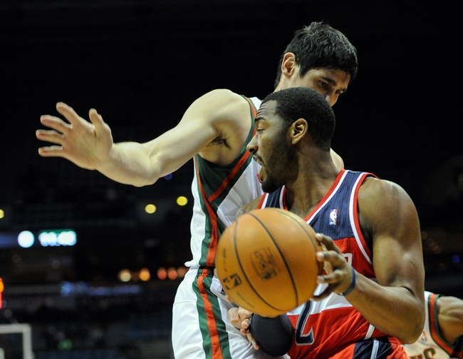 Nov 27, 2013; Milwaukee, WI, USA;  Washington Wizards guard John Wall (2) drives for the basket against Milwaukee Bucks forward Ersan Ilyasova (7) in the first quarter at BMO Harris Bradley Center. Mandatory Credit: Benny Sieu-USA TODAY Sports