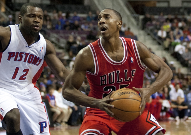 Nov 27, 2013; Auburn Hills, MI, USA; Chicago Bulls point guard Marquis Teague (25) drives to the basket as Detroit Pistons point guard Will Bynum (12) defends him during the second quarter at The Palace of Auburn Hills. Mandatory Credit: Raj Mehta-USA TODAY Sports