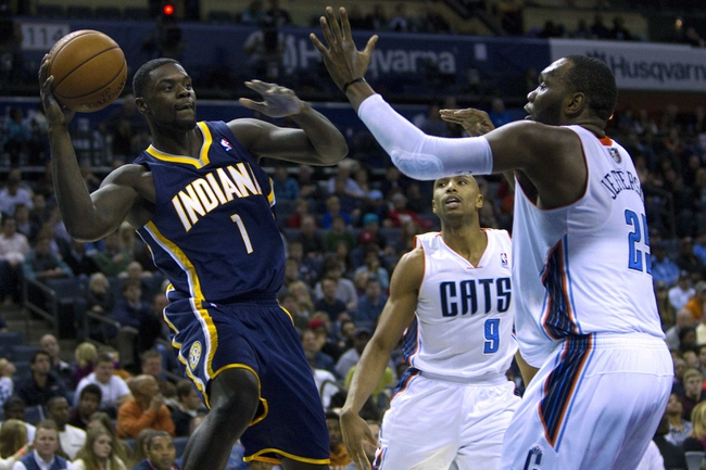 Nov 27, 2013; Charlotte, NC, USA; Indiana Pacers shooting guard Lance Stephenson (1) passes the ball while being defended by Charlotte Bobcats center Al Jefferson (25) during the fourth quarter at Time Warner Cable Arena. Pacers won 99-74. Mandatory Credit: Joshua S. Kelly-USA TODAY Sports