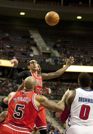 Nov 27, 2013; Auburn Hills, MI, USA; Chicago Bulls shooting guard Kirk Hinrich (12) wins a jump ball against Detroit Pistons shooting guard Kentavious Caldwell-Pope (5) during the third quarter at The Palace of Auburn Hills. Bulls beat the Pistons 99-79. Mandatory Credit: Raj Mehta-USA TODAY Sports