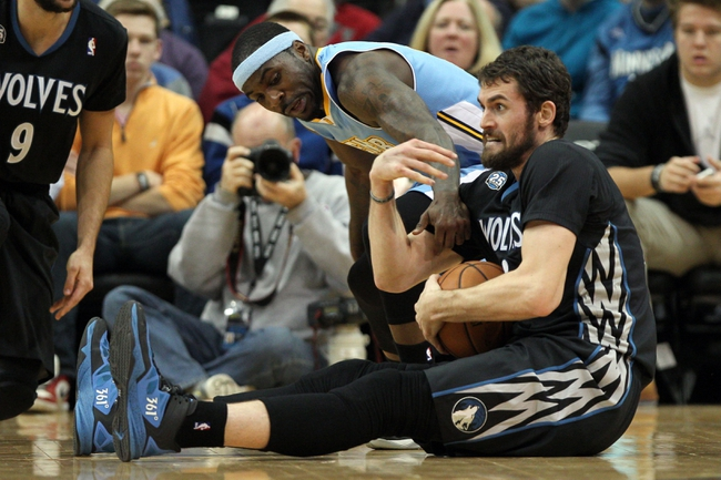 Nov 27, 2013; Minneapolis, MN, USA; Minnesota Timberwolves forward Kevin Love (42) grabs the ball away from Denver Nuggets guard Ty Lawson (3) during the third quarter at Target Center. The Nuggets defeated the Timberwolves 117-110. Mandatory Credit: Brace Hemmelgarn-USA TODAY Sports
