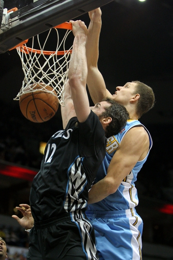 Nov 27, 2013; Minneapolis, MN, USA; Minnesota Timberwolves forward Kevin Love (42) dunks over Denver Nuggets center Timofey Mozgov (25) during the third quarter at Target Center. The Nuggets defeated the Timberwolves 117-110. Mandatory Credit: Brace Hemmelgarn-USA TODAY Sports