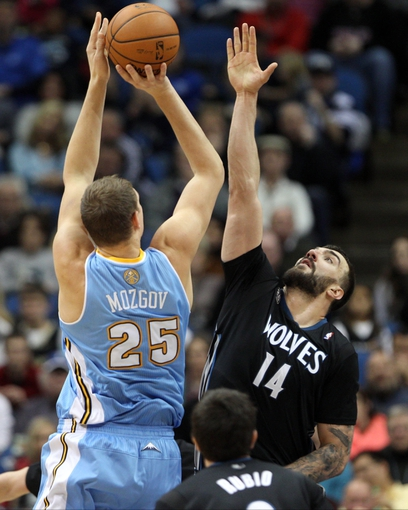Nov 27, 2013; Minneapolis, MN, USA; Denver Nuggets center Timofey Mozgov (25) shoots over Minnesota Timberwolves center Nikola Pekovic (14) during the third quarter at Target Center. The Nuggets defeated the Timberwolves 117-110. Mandatory Credit: Brace Hemmelgarn-USA TODAY Sports