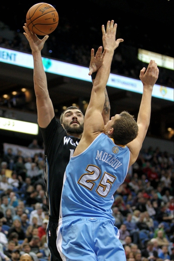 Nov 27, 2013; Minneapolis, MN, USA; Minnesota Timberwolves center Nikola Pekovic (14) shoots over Denver Nuggets center Timofey Mozgov (25) during the fourth quarter at Target Center. The Nuggets defeated the Timberwolves 117-110. Mandatory Credit: Brace Hemmelgarn-USA TODAY Sports
