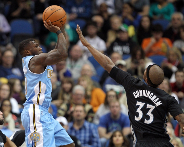 Nov 27, 2013; Minneapolis, MN, USA; Denver Nuggets guard Nate Robinson (10) shoots over Minnesota Timberwolves forward Dante Cunningham (33) during the third quarter at Target Center. The Nuggets defeated the Timberwolves 117-110. Mandatory Credit: Brace Hemmelgarn-USA TODAY Sports