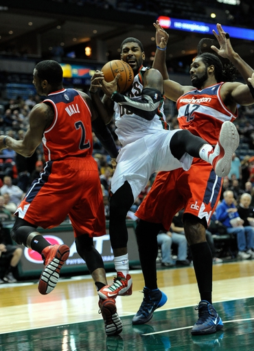 Nov 27, 2013; Milwaukee, WI, USA; Milwaukee Bucks guard O.J. Mayo (00) grabs a rebound between Washington Wizards guard John Wall (2) and forward Nene Hilario (42) in the 3rd quarter at BMO Harris Bradley Center. Mandatory Credit: Benny Sieu-USA TODAY Sports