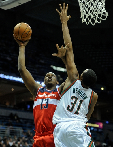Nov 27, 2013; Milwaukee, WI, USA;  Washington Wizards center Kevin Seraphin (13) takes a shot against Milwaukee Bucks forward John Henson (31) in the 2nd quarter at BMO Harris Bradley Center. Mandatory Credit: Benny Sieu-USA TODAY Sports
