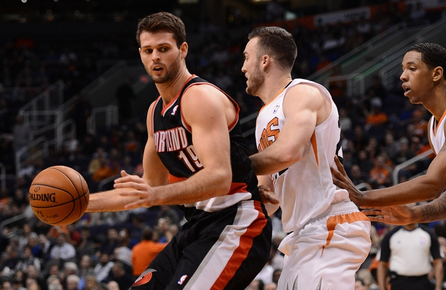 Nov 27, 2013; Phoenix, AZ, USA; Portland Trail Blazers center Joel Freeland (19) dribbles the ball in front of Phoenix Suns forward Miles Plumlee (22) in the first half at US Airways Center. The Suns won120-106.  Mandatory Credit: Jennifer Stewart-USA TODAY Sports