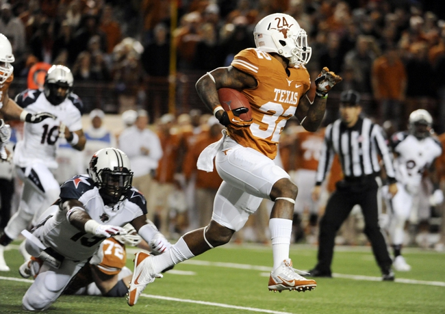 Nov 28, 2013; Austin, TX, USA; Texas Longhorns tailback Joe Bergeron (24) avoids a tackle by Texas Tech Red Raiders linebacker Sam Eguavoen (13)during the first quarter at Darrell K Royal-Texas Memorial Stadium. Mandatory Credit: Brendan Maloney-USA TODAY Sports