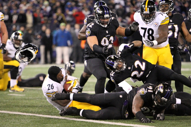 Nov 28, 2013; Baltimore, MD, USA; Pittsburgh Steelers running back LeVeon Bell (26) has his helmet knocked off by Baltimore Ravens cornerback Jimmy Smith (22) uring a NFL football game on Thanksgiving at M&T Bank Stadium. Mandatory Credit: Mitch Stringer-USA TODAY Sports