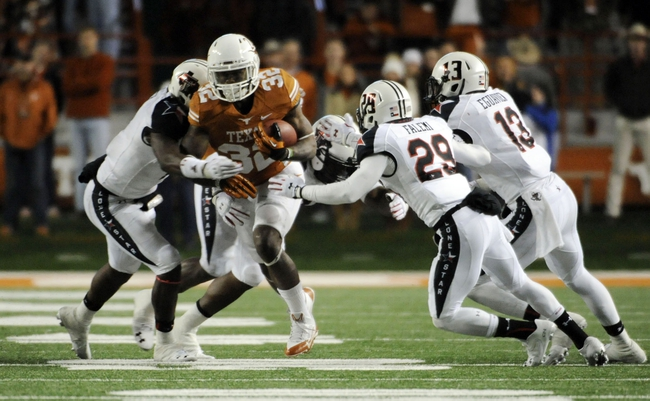 Nov 28, 2013; Austin, TX, USA; Texas Longhorns tailback Joe Bergeron (32) carries the ball against Texas Tech Red Raiders defensive linesman Kerry Hyder (left) and defensive back Olaoluwa Falemi (29) and linebacker Sam Eguavoen (13) during the second half at Darrell K Royal-Texas Memorial Stadium. Texas beat Texas Tech 41-16. Mandatory Credit: Brendan Maloney-USA TODAY Sports