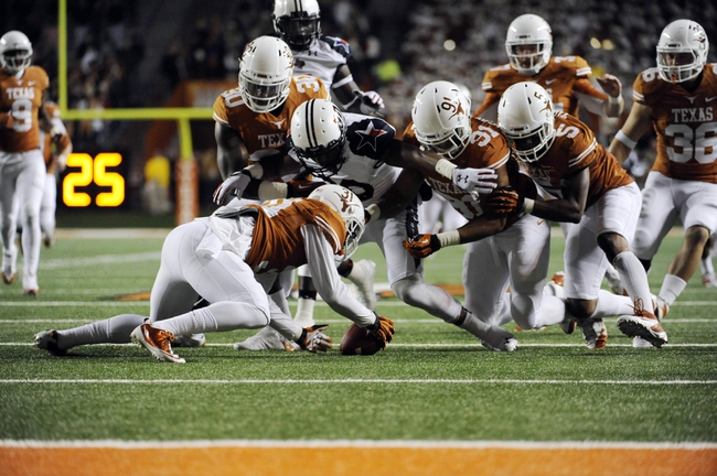 Nov 28, 2013; Austin, TX, USA; Texas Longhorns cornerback Leroy Scott (31) recovers a muffed punt with linebacker Timothy Cole (30) and defensive end Bryce Cottrell (91) and safety Josh Turner (5) and Texas Tech Red Raiders defensive back Austin Stewart (30) during the second half at Darrell K Royal-Texas Memorial Stadium. Texas beat Texas Tech 41-16. Mandatory Credit: Brendan Maloney-USA TODAY Sports