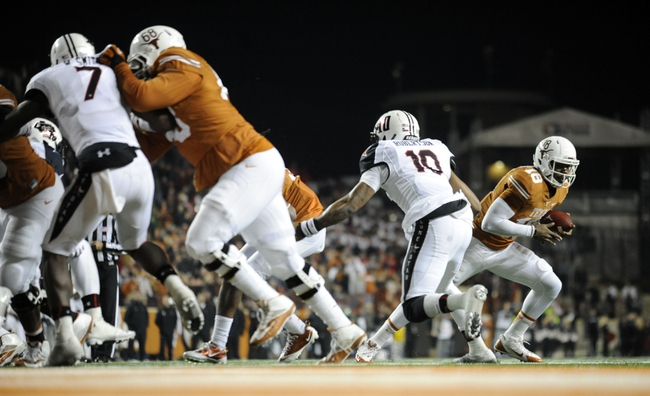 Nov 28, 2013; Austin, TX, USA; Texas Longhorns quarterback Tyrone Swoopes (18) runs the ball against the Texas Tech Red Raiders during the second half at Darrell K Royal-Texas Memorial Stadium. Texas beat Texas Tech 41-16. Mandatory Credit: Brendan Maloney-USA TODAY Sports