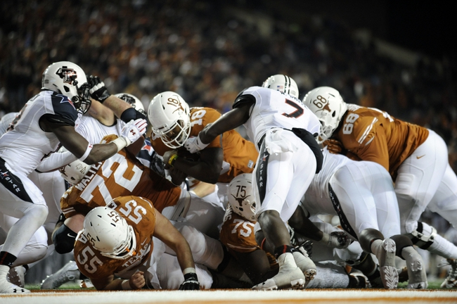Nov 28, 2013; Austin, TX, USA; Texas Longhorns quarterback Tyrone Swoopes (18) scores a touchdown against the Texas Tech Red Raiders during the second half at Darrell K Royal-Texas Memorial Stadium. Texas beat Texas Tech 41-16. Mandatory Credit: Brendan Maloney-USA TODAY Sports