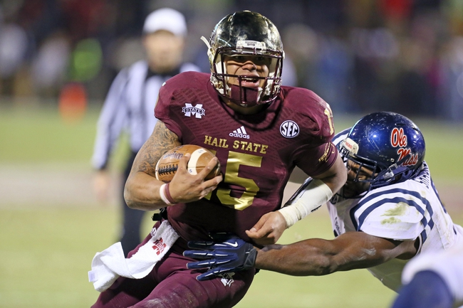 Nov 28, 2013; Starkville, MS, USA; Mississippi State Bulldogs quarterback Dak Prescott (15) advances the ball during the game against the Mississippi Rebels at Davis Wade Stadium. Mississippi State Bulldogs defeat the Mississippi Rebels with a score of 17-10 in overtime.  Mandatory Credit: Spruce Derden-USA TODAY Sports