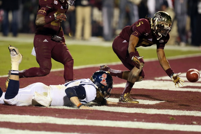 Nov 28, 2013; Starkville, MS, USA; Mississippi Rebels quarterback Bo Wallace (14) dives for the loose ball in the end zone as Mississippi State Bulldogs defensive back Jamerson Love (5) reaches for the fumble during overtime at Davis Wade Stadium. Mississippi State Bulldogs defeat the Mississippi Rebels with a score of 17-10 in overtime.  Mandatory Credit: Spruce Derden-USA TODAY Sports