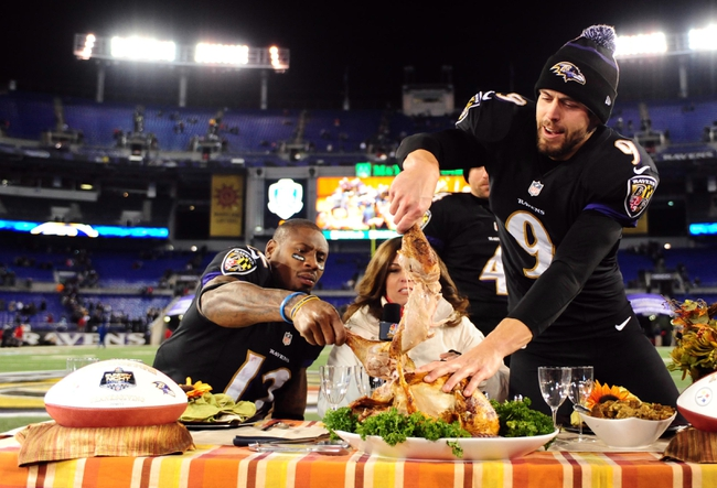 Nov 28, 2013; Baltimore, MD, USA; Baltimore Ravens kicker Justin Tucker (9) and wide receiver Jacoby Jones (12) reach for pieces of a turkey after beating the Pittsburgh Steelers 22-20 during a NFL football game on Thanksgiving at M&T Bank Stadium. Mandatory Credit: Evan Habeeb-USA TODAY Sports