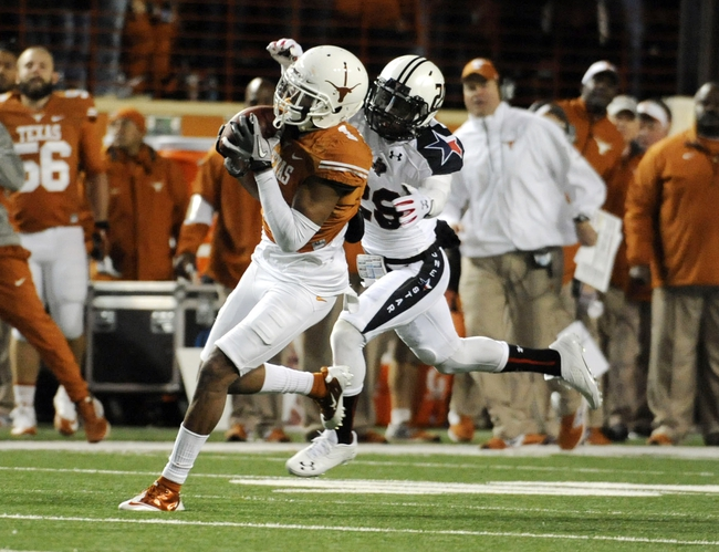 Nov 28, 2013; Austin, TX, USA; Texas Longhorns wide receiver Mike Davis (1) makes a catch ahead of Texas Tech Red Raiders defensive back Olaoluwa Falemi (29) during the first half at Darrell K Royal-Texas Memorial Stadium. Texas beat Texas Tech 41-16. Mandatory Credit: Brendan Maloney-USA TODAY Sports