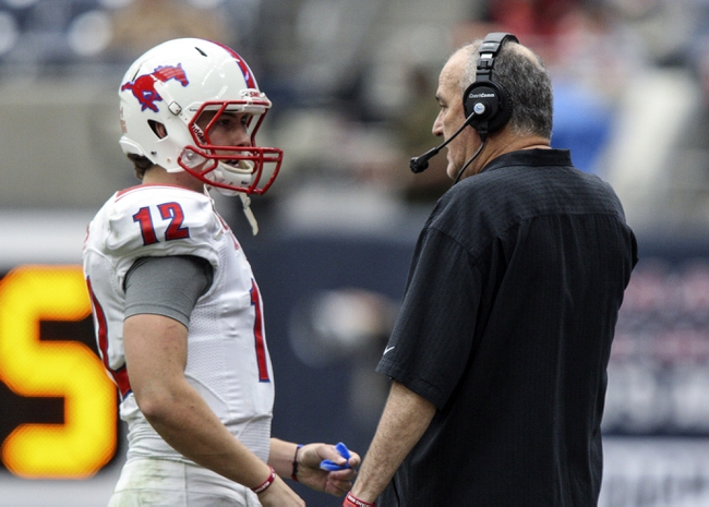 Nov 29, 2013; Houston, TX, USA; Southern Methodist Mustangs head coach June Jones talks with quarterback Neal Burcham (12) during the second quarter against the Houston Cougars at Reliant Stadium. Mandatory Credit: Troy Taormina-USA TODAY Sports