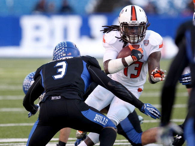 Nov 29, 2013; Buffalo, NY, USA; Bowling Green Falcons running back Travis Greene (13) runs the ball while trying to avoid a tackle by Buffalo Bulls defensive back Okezie Alozie (3) during the second half at Ralph Wilson Stadium. Bowling Green beat Buffalo 24 to 7.  Mandatory Credit: Timothy T. Ludwig-USA TODAY Sports