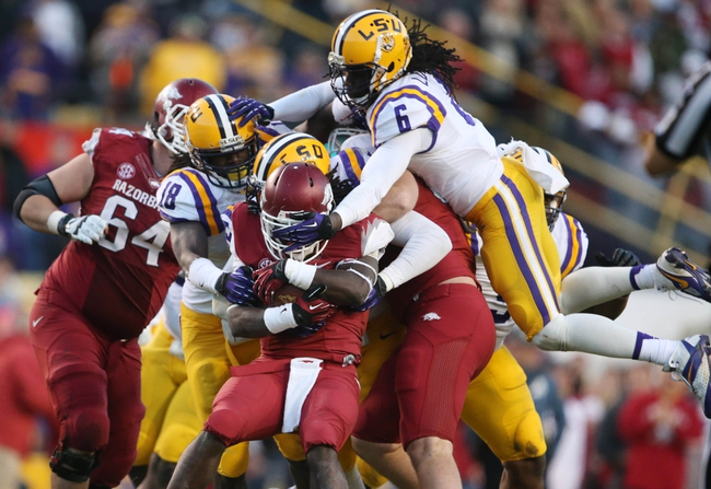 Nov 29, 2013; Baton Rouge, LA, USA; LSU Tigers safety Craig Loston (6) jumps onto the pile as Arkansas Razorbacks running back Alex Collins (3) is tackled from behind by LSU Tigers defensive end Jermauria Rasco (directly behind) and linebacker Lamin Barrow (18) at Tiger Stadium. LSU defeated Arkansas 31-27. Mandatory Credit: Crystal LoGiudice-USA TODAY Sports