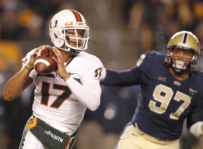 Nov 29, 2013; Pittsburgh, PA, USA; Miami Hurricanes quarterback Stephen Morris (17) scrambles with the ball as Pittsburgh Panthers defensive lineman Aaron Donald (97) pursues during the third quarter at Heinz Field. Miami won 41-31. Mandatory Credit: Charles LeClaire-USA TODAY Sports