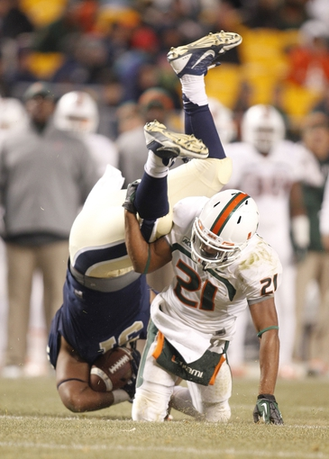 Nov 29, 2013; Pittsburgh, PA, USA; Miami Hurricanes defensive back Antonio Crawford (21) up-ends Pittsburgh Panthers fullback Jaymar Parrish (31) during the third quarter at Heinz Field. Miami won 41-31. Mandatory Credit: Charles LeClaire-USA TODAY Sports