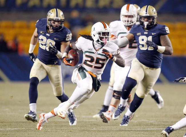Nov 29, 2013; Pittsburgh, PA, USA; Miami Hurricanes running back Dallas Crawford (25) carries the ball against the Pittsburgh Panthers during the third quarter at Heinz Field. Miami won 41-31. Mandatory Credit: Charles LeClaire-USA TODAY Sports