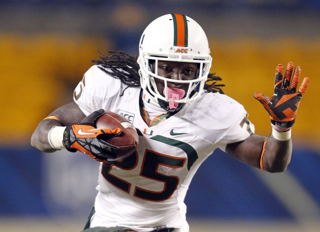 Nov 29, 2013; Pittsburgh, PA, USA; Miami Hurricanes running back Dallas Crawford (25) rushes the ball against the Pittsburgh Panthers during the third quarter at Heinz Field. Miami won 41-31. Mandatory Credit: Charles LeClaire-USA TODAY Sports