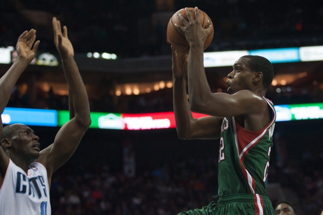 Nov 29, 2013; Charlotte, NC, USA; Milwaukee Bucks power forward Khris Middleton (22) goes up for a shot over Charlotte Bobcats center Bismack Biyombo (0) during the first half at Time Warner Cable Arena. Mandatory Credit: Jeremy Brevard-USA TODAY Sports