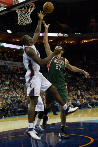 Nov 29, 2013; Charlotte, NC, USA; Charlotte Bobcats center Bismack Biyombo (0) knocks the shot away by Milwaukee Bucks center Zaza Pachulia (27) during the first half at Time Warner Cable Arena. Mandatory Credit: Jeremy Brevard-USA TODAY Sports