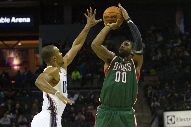 Nov 29, 2013; Charlotte, NC, USA; Milwaukee Bucks shooting guard O.J. Mayo (00) shoots the ball over Charlotte Bobcats point guard Ramon Sessions (7) during the first half at Time Warner Cable Arena. Mandatory Credit: Jeremy Brevard-USA TODAY Sports