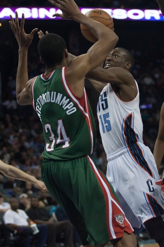 Nov 29, 2013; Charlotte, NC, USA; Charlotte Bobcats point guard Kemba Walker (15) shoots the ball over Milwaukee Bucks shooting guard Giannis Antetokounmpo (34) at Time Warner Cable Arena. Bobcats defeated the Bucks 92-76. Mandatory Credit: Jeremy Brevard-USA TODAY Sports