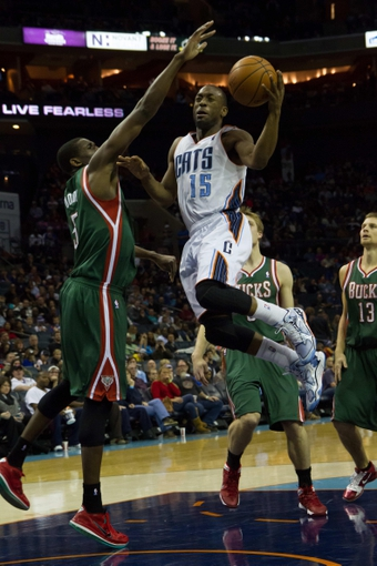Nov 29, 2013; Charlotte, NC, USA; Charlotte Bobcats point guard Kemba Walker (15) goes up for a shot while Milwaukee Bucks power forward Ekpe Udoh (5) defends during the second half at Time Warner Cable Arena. Bobcats defeated the Bucks 92-76. Mandatory Credit: Jeremy Brevard-USA TODAY Sports