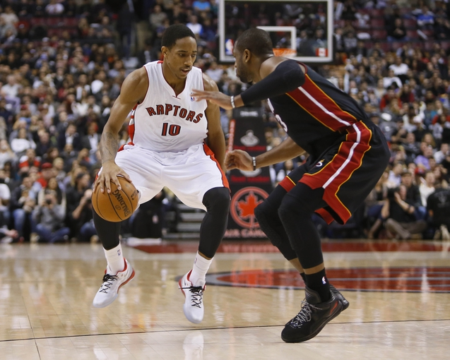 Nov 29, 2013; Toronto, Ontario, CAN; Toronto Raptors guard DeMar DeRozan (10) tries to get around Miami Heat guard Dwyane Wade (3) during the first half at the Air Canada Centre. Mandatory Credit: John E. Sokolowski-USA TODAY Sports