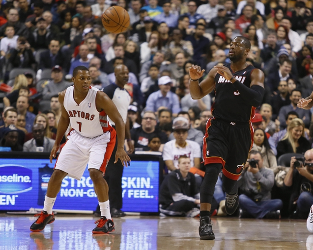 Nov 29, 2013; Toronto, Ontario, CAN; Miami Heat guard Dwyane Wade (3) receives a pass as Toronto Raptors guard Kyle Lowry (7) looks on during the first half at the Air Canada Centre. Mandatory Credit: John E. Sokolowski-USA TODAY Sports