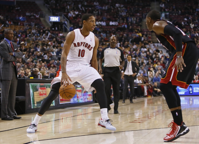 Nov 29, 2013; Toronto, Ontario, CAN; Toronto Raptors guard DeMar DeRozan (10) dribbles the ball against Miami Heat guard Mario Chalmers (15) during the first half at the Air Canada Centre. Mandatory Credit: John E. Sokolowski-USA TODAY Sports