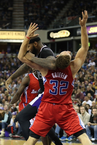 Nov 29, 2013; Sacramento, CA, USA; Sacramento Kings center DeMarcus Cousins (15) commits an offensive foul against Los Angeles Clippers power forward Blake Griffin (32) during the fourth quarter at Sleep Train Arena. The Los Angeles Clippers defeated the Sacramento Kings 104-98 in overtime. Mandatory Credit: Kelley L Cox-USA TODAY Sports