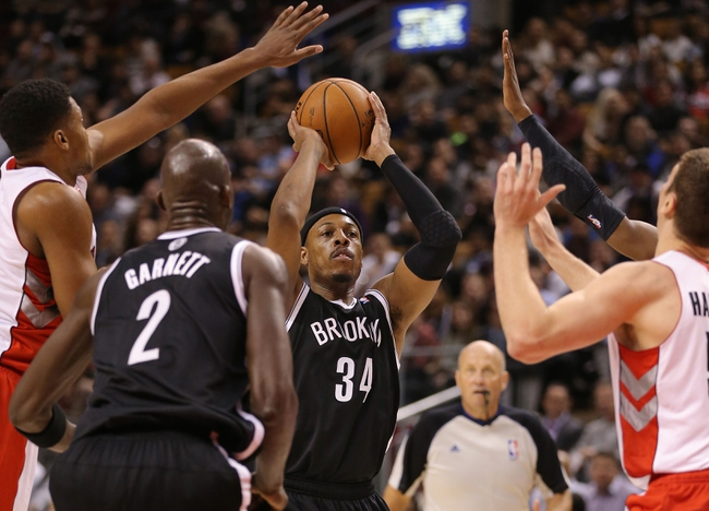 Nov 26, 2013; Toronto, Ontario, CAN; Brooklyn Nets forward Paul Pierce (34) shoots as forward Kevin Garnett (2) watches and Toronto Raptors forward Rudy Gay (22) tries to block the shot at Air Canada Centre. The Nets beat the Raptors 102-100. Mandatory Credit: Tom Szczerbowski-USA TODAY Sports