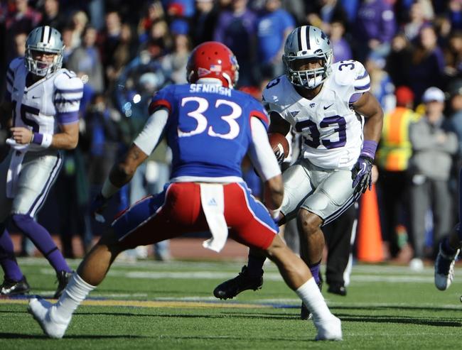 Nov 30, 2013; Lawrence, KS, USA; Kansas State Wildcats running back John Hubert (33) is tackled by Kansas Jayhawks linebacker Cassius Sendish (33) in the first half at Memorial Stadium. Mandatory Credit: John Rieger-USA TODAY Sports