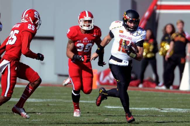 Nov 30, 2013; Raleigh, NC, USA; Maryland Terrapins quarterback C.J. Brown (16) runs the ball as North Carolina State Wolfpack defenders Brandon Pittman (39) and Dontae Johnson (25) pursue during the first half at Carter Finley Stadium. Mandatory Credit: Rob Kinnan-USA TODAY Sports
