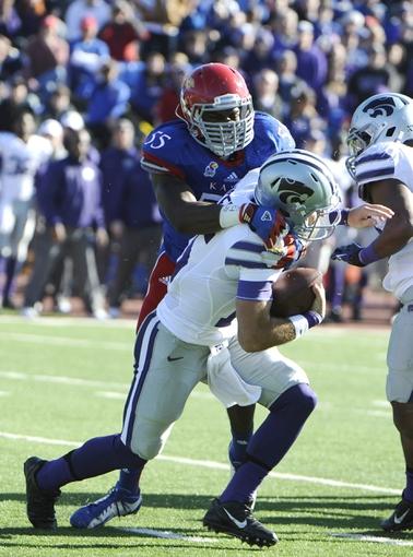 Nov 30, 2013; Lawrence, KS, USA; Kansas State Wildcats quarterback Jake Waters (15) is sacked by Kansas Jayhawks linebacker Michael Reynolds (55) in the first half at Memorial Stadium. Mandatory Credit: John Rieger-USA TODAY Sports