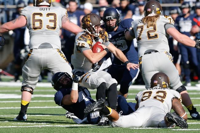 Nov 30, 2013; Logan, UT, USA; Wyoming Cowboys quarterback Brett Smith (16) is sacked by Utah State Aggies linebacker Nick Vigil (41) during the first quarter at Romney Stadium. Mandatory Credit: Chris Nicoll-USA TODAY Sports