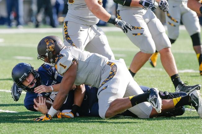 Nov 30, 2013; Logan, UT, USA; Utah State Aggies quarterback Darell Garretson (6) is tackled by Wyoming Cowboys linebacker Jordan Stanton (1) during the first quarter at Romney Stadium. Mandatory Credit: Chris Nicoll-USA TODAY Sports