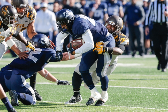 Nov 30, 2013; Logan, UT, USA; Utah State Aggies running back Joey DeMartino (28) is tackled by Wyoming Cowboys linebacker Malkaam Muhammad (9) during the second quarter at Romney Stadium. Mandatory Credit: Chris Nicoll-USA TODAY Sports