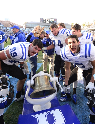 Nov 30, 2013; Chapel Hill, NC, USA;  Duke Blue Devils tight end Braxton Deaver (89) and guard Dave Harding (74) and wide receiver Brandon Braxton (5) with the victory bell after the game. The Duke Blue Devils defeated the North Carolina Tar Heels 27-25 at Kenan Memorial Stadium. Mandatory Credit: Bob Donnan-USA TODAY Sports