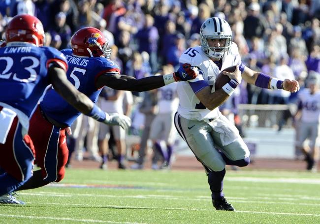 Nov 30, 2013; Lawrence, KS, USA; Kansas State Wildcats quarterback Jake Waters (15) is tackled by Kansas Jayhawks linebacker Michael Reynolds (55) in the second half at Memorial Stadium. Kansas State won the game 31-10. Mandatory Credit: John Rieger-USA TODAY Sports